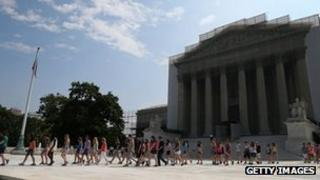 Tourists walk out in front of the US Supreme Court building 17 June 2013