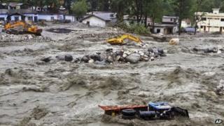Bulldozer and other vehicles are drifted in a flooded river in Uttarkashi district, India, Monday, June 17, 2013