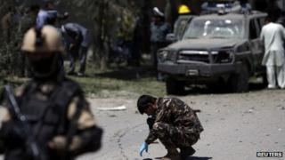 Afghan security forces personnel investigate the site of the explosion in Kabul on 18 June 2013