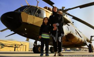 Latifa and Malalai Nabizada standing in front of a helicopter