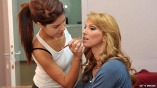 A make-up artist work on Elena Skordelli prior to her arrest