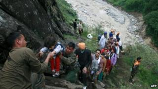 Indian army officials help travellers and villagers up a steep slope after they were stranded by the rising floodwaters of the River Alaknanda near Govindghat, Chamoli District in the northern Indian state of Uttarakhand on June 18