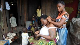 A woman gets her hair done in a shanty town in Lagos, Nigeria (30 August 2012)