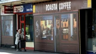 "A woman walks past the ""Roasta Coffee"" outlet at Coronation Square shopping centre in Hester's Way, Cheltenham"
