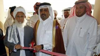 "Qatari Assistant Minister for Foreign Affairs Ali bin Fahd al-Hajri (C) cuts the ribbon alongside a member of the Taliban""s office Jan Mohammad Madani (L) at the opening ceremony of the new Taliban political office in Doha"