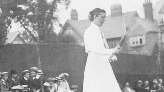 An unnamed lady about to serve at doubles, around 1904