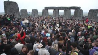Crowds gather at dawn amongst the stones at Stonehenge
