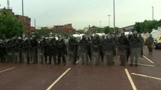 Police in riot gear keeping rival groups apart