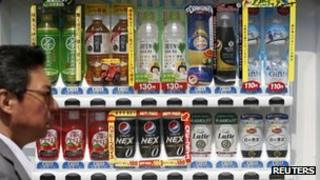 A man walks past a Suntory beverage vending machine