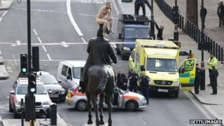 Dan Motrescu sits on top of the statue naked