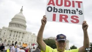 """Demonstrators with the Tea Party protest the Internal Revenue Service (IRS) targeting of the Tea Party and similar groups during a rally called """"Audit the IRS"""" outside the US Capitol in Washington, DC 19 June 2013"""