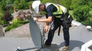 Technician installing Sky dish