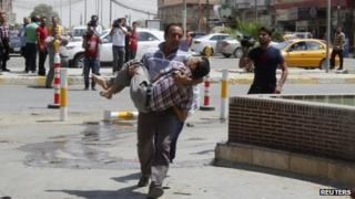 A man wounded by a suicide bomber in Tuz Khurmato city is carried to a hospital