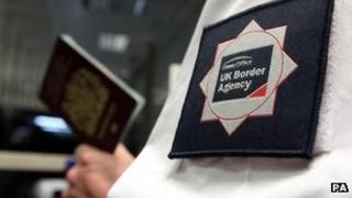 A UK Border Agency worker holding a passport