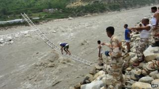 Members of the Indo Tibetan Border Police (ITBP) rescue stranded people with the help of mountaineering ropes and ladders in Uttarkashi in Uttarakhand state