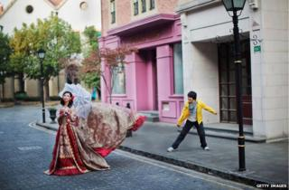 A woman dressed in a red dress walking in Thames Town, China
