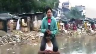 Narayan Pargaien on shoulders of a man who is standing in flood waters