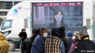 Japanese people stand in front of a large TV screen showing Japanese news