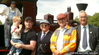 John Travolta holding his son with railway staff in front of a steam train
