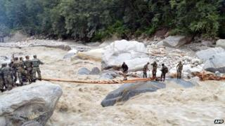 Indian defence personnel assist stranded civilians in crossing a raging river near the Pindari Glacier area of northern Uttarakhand state on 27 June 2013