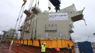 The AFT island is lowered into place on HMS Queen Elizabeth aircraft carrier at Rosyth Dockyard