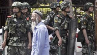 Armed police officers stand guard near the Erdaoqiao Bazaar in Urumqi (June 29, 2013)