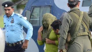 Pakistani security personnel move Rimsha Masih (2L), a Christian girl accused of blasphemy, to a helicopter after her release from jail in Rawalpindi on September 8, 2012.