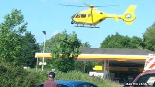 Air ambulance flying over petrol station