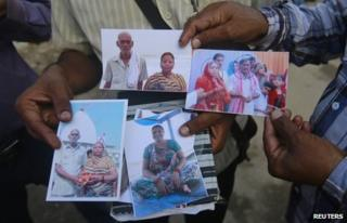 Relatives of missing people, affected by the flash floods and landslides, display their photographs outside the Indian Air Force base in Dehradun, in the Himalayan state of Uttarakhand June 26, 2013