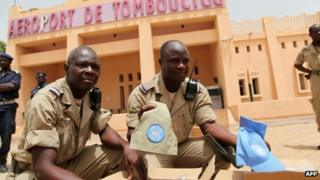 Members of the security forces hold up UN caps and insignia outside the airport of Timbuktu on 30 June 2013
