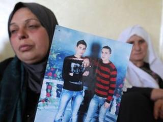 The mother of Moataz Sharawna holds up a picture of him (right, in red and black jumber) (2 July 2013)