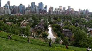 Residents take a higher ground to watch the flood situation near the flooded Bow River in Calgary, Alberta, 22 June 2013