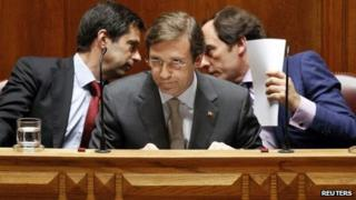 Paulo Portas (R) talks to ex-Finance Minister Vitor Gaspar (L) behind Prime Minister Pedro Passos Coelho June 25, 2012