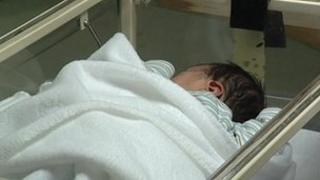 Baby in hospital cot