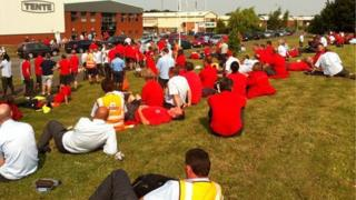 Staff sitting on grass outside sorting office