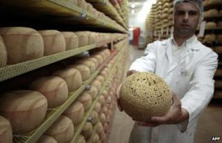 A cheesemonger holds a 24-month old mimolette cheese at a production site in Isigny-sur-Mere, north-western France, 4 July