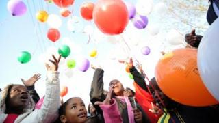 Kids release balloons after a prayer for former South African President Nelson Mandela on July 5, 2013 outside the Medi Clinic Heart Hospital where Mandela is hospitalized in Pretoria.