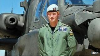 Prince Harry in front of an Apache helicopter