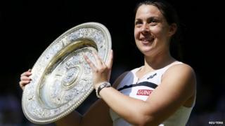 Marion Bartoli lifts Wimbledon trophy.