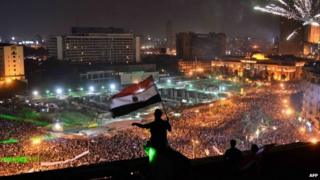 Egyptians wave national flag on rooftop as thousands demonstrate in Tahrir square