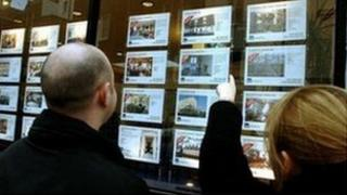 Couple studying estate agent's notices