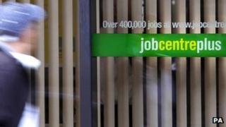 Man walking past a Job Centre Plus sign