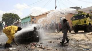 """Firefighters extinguish a fire from a ruined car after an explosion near the main market in Somalia""""s capital Mogadishu July 9, 2013."""