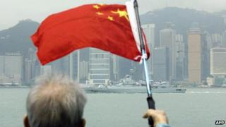 File photo: An elderly supporter waves a Chinese flag as a ship from a Chinese People Liberation Army Navy task group passes the Victoria harbour skyline in Hong Kong, 5 May 2004