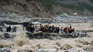 In this photograph taken on June 23, 2013, stranded Indian pilgrims wait to be rescued on the side of a river at Govind Ghat. Authorities on July 9, 2013
