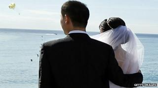 A Chinese couple pose for a wedding photograph on the Promenade des Anglais in Nice, France