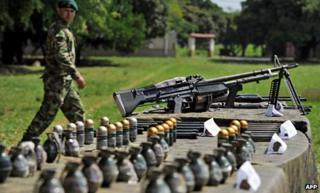 A Colombian soldier walks next to seized weapons in Cali, in December last year