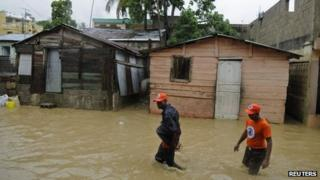 Men walk through floodwaters caused by Tropical Storm Chantal in Santo Domingo, capital of the Dominican Republic (10 July 2013)