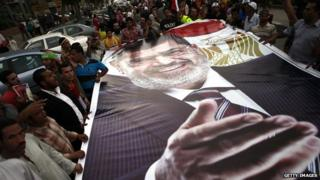 Mohammed Morsi supporters holding a large poster of the ousted president (7 July 2013)