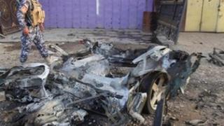 Policeman walks past car destroyed in Kirkuk attack (11/07/13)